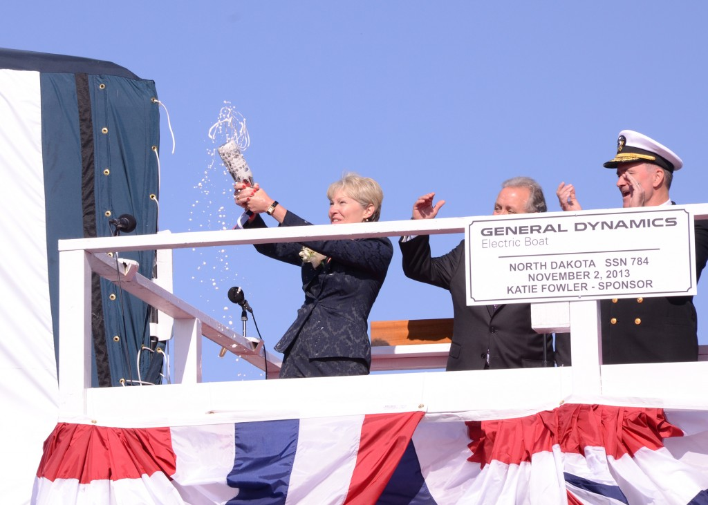 Ship sponsor Katie Fowler, wife of retired Vice Adm. Jeff Fowler, christens Pre-Commissioning Unit North Dakota (SSN 784) by breaking a bottle of sparkling wine against the back of the sail. (U.S. Navy Photo 131102-N-SF554-119)