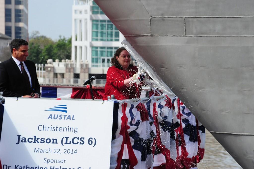Dr. Katherine Holmes Cochran, breaks a bottle across Jackson's bow during a christening ceremony at Austal USA shipyard in Mobile, Ala. (U.S. Navy photo 140322-O-ZZ999-202 courtesy of Austal U.S.A.)