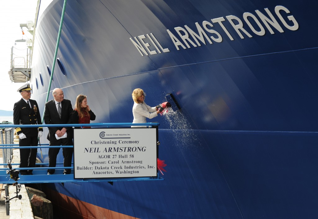 Carol Armstrong, ship's sponsor for the Auxiliary General Oceanographic Research (AGOR) research vessel (R/V) Neil Armstrong (AGOR 27), breaks a bottle across bow during a christening ceremony at Dakota Creek Industries, Inc. shipyard in Anacortes, Wash. Joining Armstrong on the platform are Rear Adm. Matthew Klunder, left, chief of naval research, Mr. Dick Nelson, president, Dakota Creek Industries, Inc., and Kali Armstrong, granddaughter of the late astronaut. (U.S. Navy photo 140329-N-PO203-336)