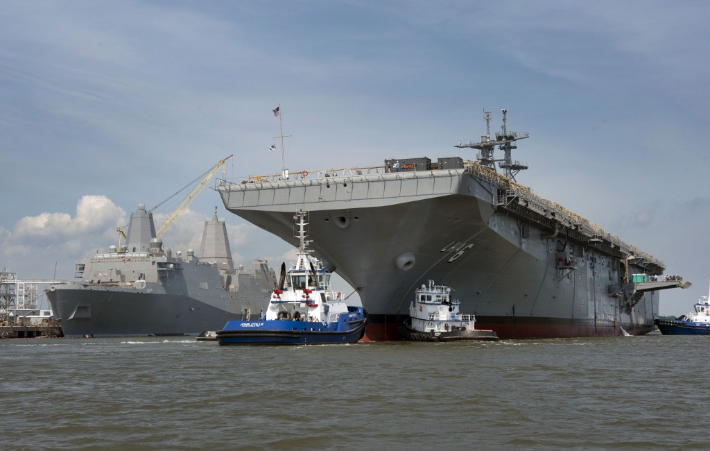 Tugboats guide the amphibious assault ship Pre-Commissioning Unit (PCU) America (LHA 6) to her berthing place at Ingalls Shipbuilding. The Ingalls-built amphibious transport dock ship Pre-Commissioning Unit (PCU) Arlington (LPD 24) can be seen in the background. America will be christened Oct. 20. (U.S. Navy photo courtesy of Ingalls Shipbuilding/Released)