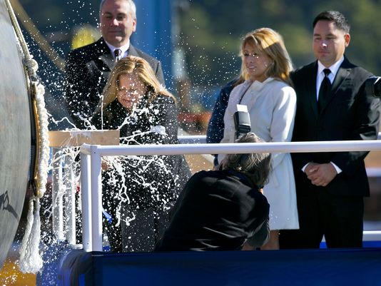 Rosa Peralta smashes a bottle of Champagne to christen the USS Raphael Peralta, the 35th Arleigh Burke Class Missile Destroyer to be built by Bath Iron Works, Oct. 31, 2015, in Bath, Maine. (Photo: Robert F. Bukaty/AP)